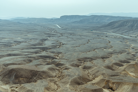 Sunny landscape view of dry desert near the dead sea in Israel. Infinity valley panorama of lone sand, rocks, hills and stones. Waterless middle east territory, silence and heat. Stock Photo