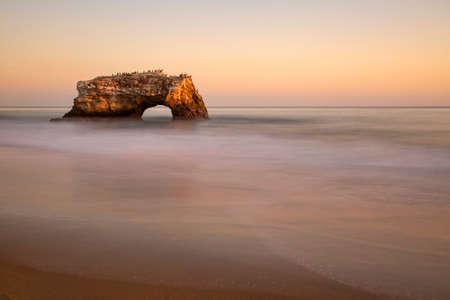 A natural rock arch at Natural Bridges State Park in Santa Cruz, California. Long exposure at sunset.