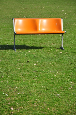 Orange bench on lawn photo