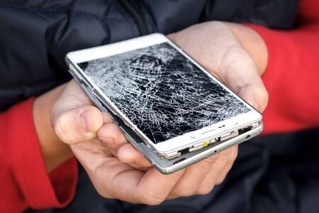 Children hands holding broken mobile smartphone. Phone screen is badly damaged. Connection not possible