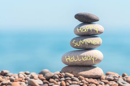 Stacked stone tower with inscription happy summer holidays. Colored pebble and sea. Vacation concept. Balance, zen and equilibrium