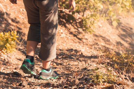 Hiking in mountains or forest with sport hiking shoes. Girl hiker walks along wild path in remote area. Trekking on rocky road