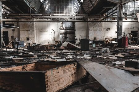 Pile of garbage and items on floor of abandoned ruined building. Horrible interior of old factory. Empty industrial gloomy house