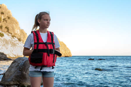 Young girl in red life jacket stands on beach with rock and sea. Female lifeguard on duty of coast. Water safety concept