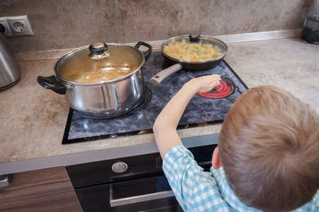 Kid risking accident with cooker in kitchen. Hazard at home. Concept of burn children. Warning burning human skin.