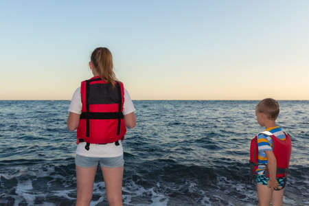 Two children standing in the beach wearing red life-jackets at sunset. Sea gale and people in life vest on shore. Stock Photo