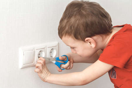 Little boy plays with electric socket and scissors. High voltage hazard.