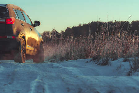 Car with winter tires and tyre trail on winter rough road in snow season. Banque d'images - 157870050