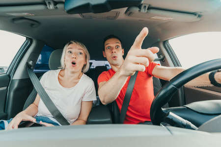 Surprised man and impressed woman point fingers at incredible accident while driving car. Shocked people with wide open eyes and mouths. Excited faces of people with OMG emotion.