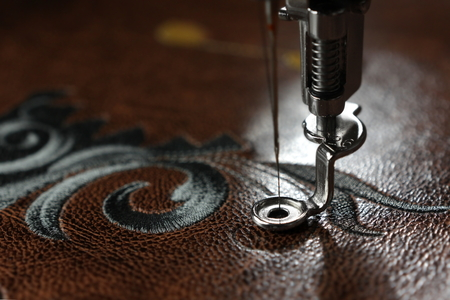 Multilayer embroidery on brown leatherette with embroidery machine - close up with needle up - background blanked out blurry