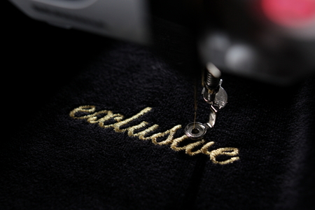"embroidery of gold lettering ""exclusive"" on black velvety fabric with embroidery machine - diagonal view with part of machine - background and foreground blanked out blurry"