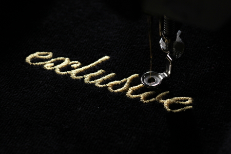 embroidery of gold lettering exclusive on black velvety fabric with embroidery machine - diagonal top view from right