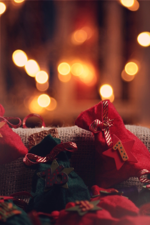 part view on traditional advent calendar with small fabric bags for individual filling in front of a warm illuminated background - candle light mood, background blanked out blurry - bags filled with christmas almond cookie
