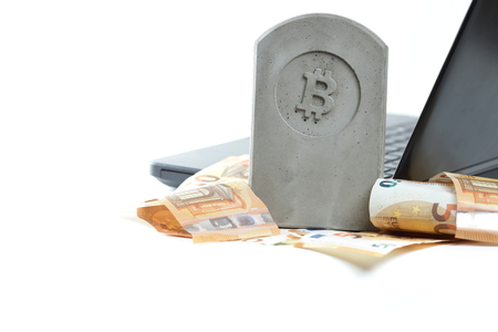 stone monument/tombstone with bitcoin symbol standing on a pile of banknotes in front of a black notebook on white background - copy space for text on left side