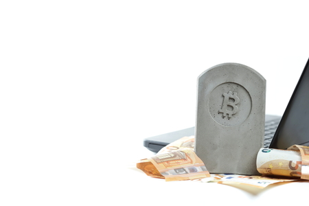stone monumenttombstone with bitcoin symbol standing on a pile of banknotes in front of a black notebook on white background - panel type composition with copy space for text on left side