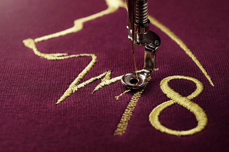 Embroidery with embroidery machine of dog silhouette and number 2018 in gold on claret fabric - chinese new year concept - close up view on process of atin stitch