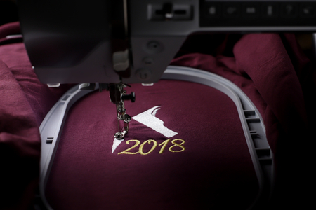 Embroidery with embroidery machine of dog head and number 2018  in silver and gold on claret fabric - chinese new year concept - overview on stitching, machine and hoop