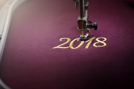 Embroidery with embroidery machine of number 2018  in gold on claret fabric - chinese new year concept - front view on stitching and hoop in bright luxury light mood