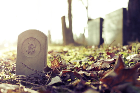 stone monumenttombstone with bitcoin symbol standing on cementery - vintagechrome look - sunny blurred background - economicfinancial concept