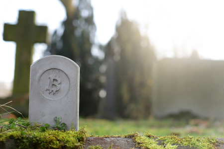 stone monumenttombstone with bitcoin symbol on cementery - sunny blurred background with space for text - economicfinancial concept