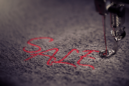 embroidery of red lettering SALE on soft grey fabric with embroidery machine - colored close up - background and foreground blanked out blurry - marketing and business concept
