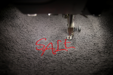 embroidery of red lettering SALE on soft grey fabric with embroidery machine - top view with moving needle bar- background and foreground blanked out blurry - marketing and business concept