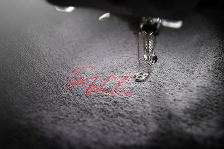 embroidery of red lettering SALE on soft grey fabric with embroidery machine - part view on font and machine head - background and foreground blanked out blurry - marketing and business concept 版權商用圖片