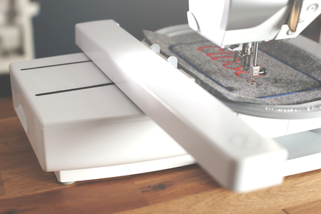 view on a modern computerised sewing machine and embroidery unit with needle down stitching red lettering on grey felt in a stylish work environment - matte look