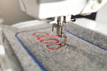 diagonal detail view on a modern computerised sewing machine and embroidery unit stitching red lettering on grey felt in bright light