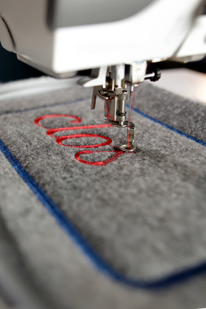 closeup on grey felt with red lettering stitched by a modern computerised sewing machine with embroidery unit for decorative purpose - portrait orientation