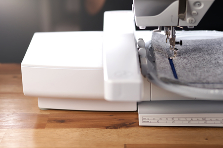 modern computerised sewing machine with embroidery unit standing on a warm wooden surface in bright light stitching a blue frame on grey felt - friendly and stylish work environment concept Stockfoto