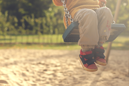Child having fun with swing on a playground in bright afternoon sun - legs angled - matte look