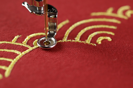 Embroidery of traditional shell pattern with gold on red fabric by modern embroidery machine - chinese new year concept - close up view on process of satin stitch 版權商用圖片