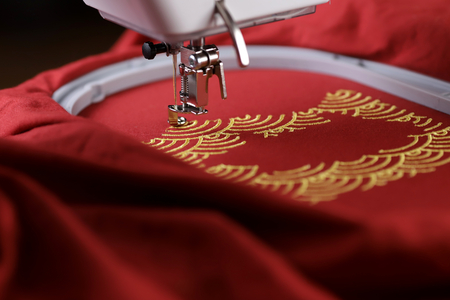 Embroidery of traditional shell pattern framing pig outline with gold on red fabric by modern embroidery machine - chinese new year concept - view on stitching area from back of machine in studio light 版權商用圖片