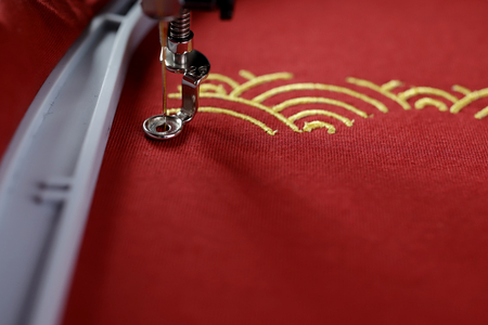 Embroidery of traditional shell pattern with gold on red fabric by modern embroidery machine - chinese new year concept - view on process of satin stitch, machine foot and hoop - copy space for text 版權商用圖片