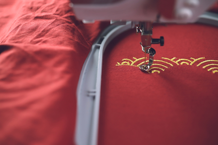 Embroidery of traditional shell pattern with gold on red fabric by modern embroidery machine - chinese new year concept - view on machine head, sewing foot and hoop at process of satin stitch in bright light 版權商用圖片