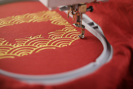 Oblique view on embroidery of traditional shell pattern framing pig outline with gold on red fabric by modern embroidery machine - chinese new year concept - view on stitching area with needle moving down 版權商用圖片