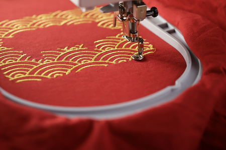 Oblique view on embroidery of traditional shell pattern framing pig outline with gold on red fabric by modern embroidery machine - chinese new year concept - view on stitching area with hoop and machine foot