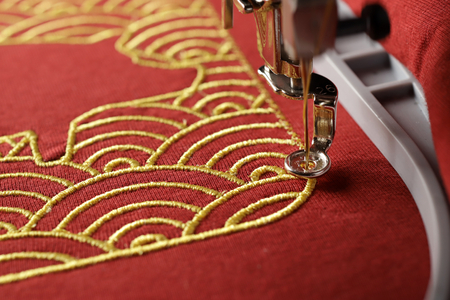 Close up view on embroidery of traditional shell pattern framing pig outline with gold on red fabric by modern embroidery machine - chinese new year concept - progress of satin border stitched near embroidery hoop