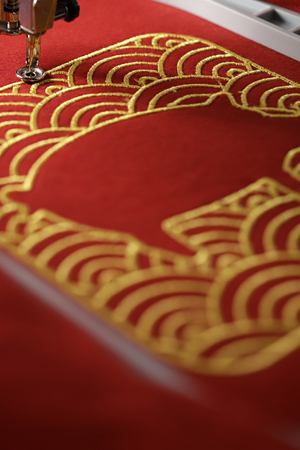 Embroidery of traditional shell pattern and stitched pig outline with gold on red fabric by modern embroidery machine - chinese new year concept - finishing of satin outline with needle down - portrait orientation, foreground blanked out blurry 版權商用圖片