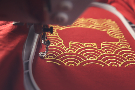 Embroidery of traditional shell pattern framing pig outline with gold on red fabric by modern embroidery machine in festive light mood - chinese new year concept - progress of underlay of satin border - background blanked out blurry 版權商用圖片