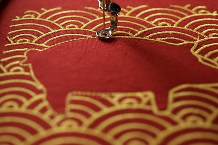 Close up of pig embroidery framed by traditional shell pattern with gold on red fabric - chinese new year concept - progress of satin stitch around pig - foreground blanked out blurry