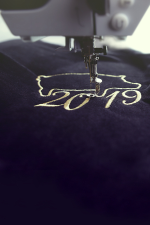 2019 chinese new year motive stitched by embroidery machine with precious gold yarn on black velvetely fabric - portrait orientation in vintage coloring 版權商用圖片