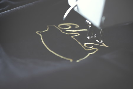 Embroidery machine stitching 2019 chinese new year motive with precious gold yarn on black velvetely fabric in dark misty light mood - backside view - season gift concept