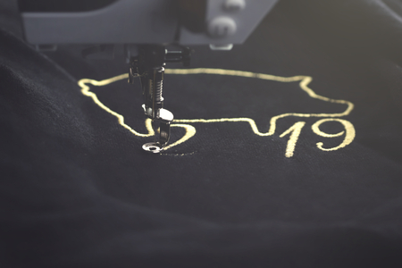 2019 chinese new year motive stitched with precious gold yarn on black velvetely fabric by embroidery machine in misty light mood - tilted front view of progress