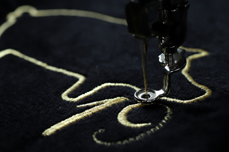 Macro view on 2019 chinese new year motive stitched by embroidery machine with precious gold yarn on black velvetely fabric - oblique view on progress with needle down and blurred background