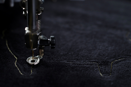 Detail view on embroidery machine stitching outline of a pig on black velvetely fabric in dark light mood - 2019 chinese new year concept, blurred background, needle down