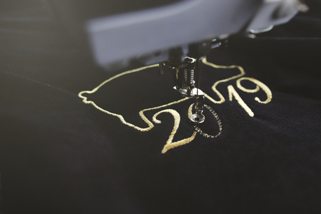 Embroidery machine stitching 2019 chinese new year motive with precious gold yarn on black velvet in dark misty light mood - oblique view with blurred background