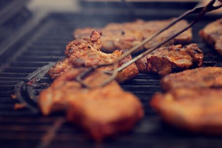 closeup on crispy grilled meat that is grilled on hot cast-iron grate - realistic food and barbecue party concept - foreground and background blanked out blurry Banco de Imagens - 132046205
