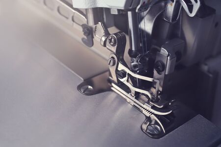 Mechanism of an industrial overlock sewing machine - closeup view in dark light mood on foot and needles with blurred background - copy space for text